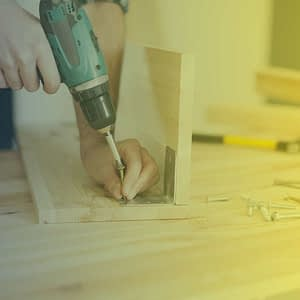 a man working with a drill and wood