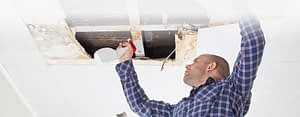 man removing mold in home in the ceiling
